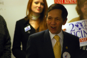 Rep. Dennis Kucinich speaks to Democratic supporters. Even in very soft focus in the background, his wife draws the eye, as if to a flower.