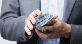 Man holds paycheck advance cash